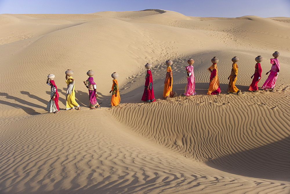 Women bear the responsibility of fetching water from the sparse wells within Rajasthan's vast Thar Desert. Trekking up the side of a sand dune, women expertly balance large clay water vessels atop their heads. Rajasthan, India, Thar Desert, Rajasthan, India