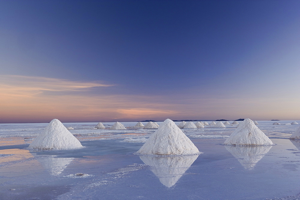 The salt pans of Salar de Uyuni, with shallow water and mineral deposits. White salt granules raked into heaps, Salar de Uyuni, Bolivia