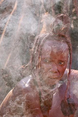Himba woman at campfire, Puros Conservancy, Damaraland, Namibia