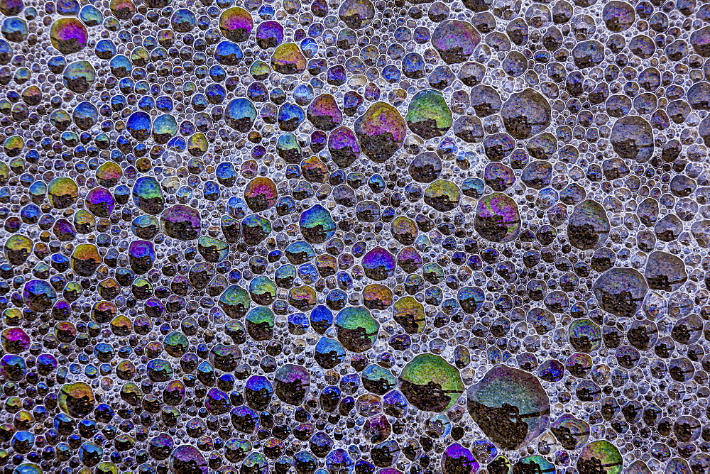 Froth and bubbles of air reflecting rainbow colours on the surface at Cannon Beach, Oregon, USAAstoria, Oregon, USA