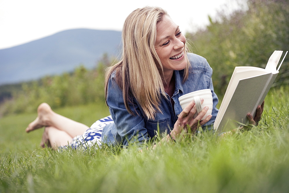 A woman lying on the grass holding a tea cup and reading a book.