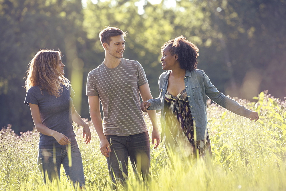 Three people, a man and two women walking through tall grass in a meadow.