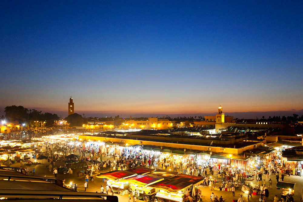 A few over the illuminated Djemaa el-Fna market square at sunset in Marrakesh, Morocco