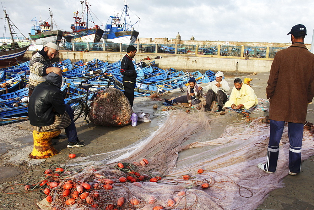 Fishermen patching nets in the busy fishing harbour of the former Portuguese colony, Essaouira, Morocco