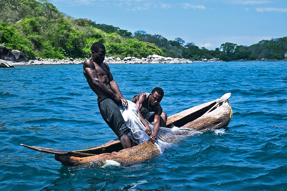 Fishermen pulling in nets in a dugout canoe on Lake Malawi (East Africa)
