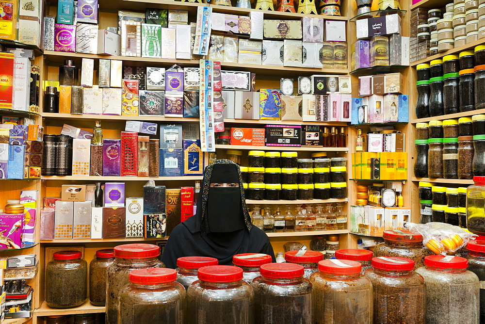 Woman wearing burka selling perfumes in Oman