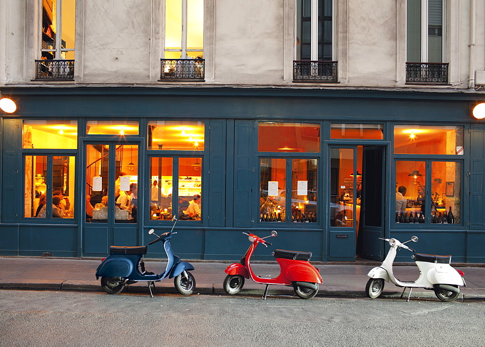 Row of vespas parked against exterior of Cafe Marly Restaurant, Paris