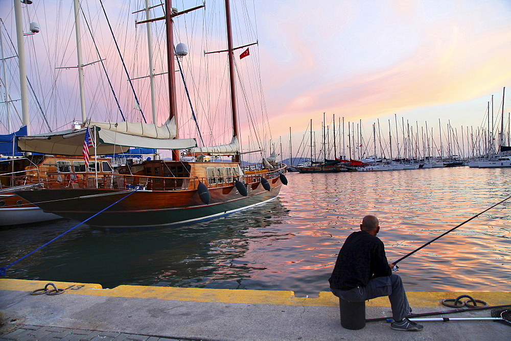 Man fishing at harbor at sunset in Bodrum Peninsula, Turkey