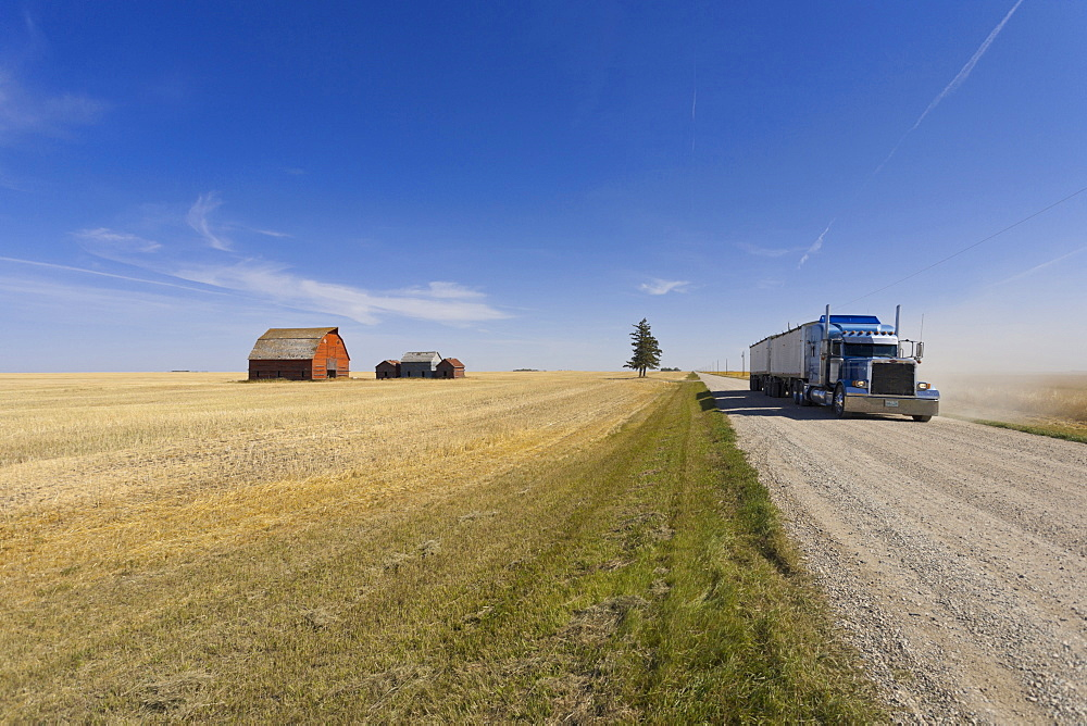 View of farmer house, landscape and trucks on road, Saskatchewan, Canada