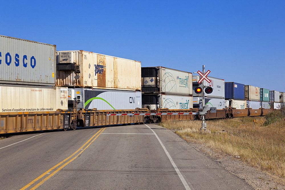 View of cargo train crossing railroad on Highway 15, Saskatchewan, Canada
