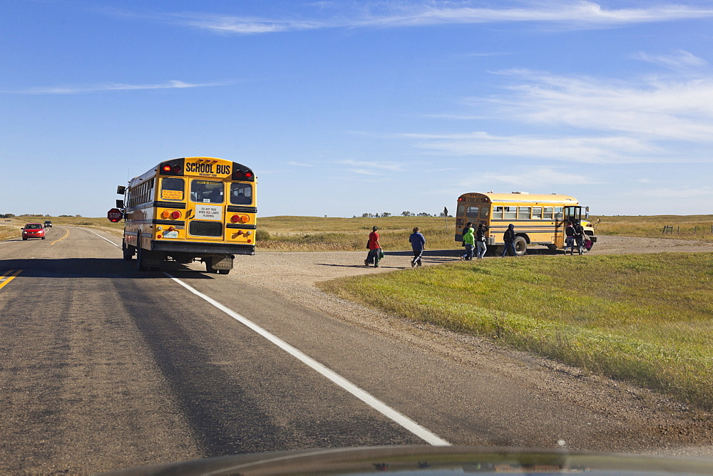 Children at school bus on Highway 15, Saskatchewan, Canada