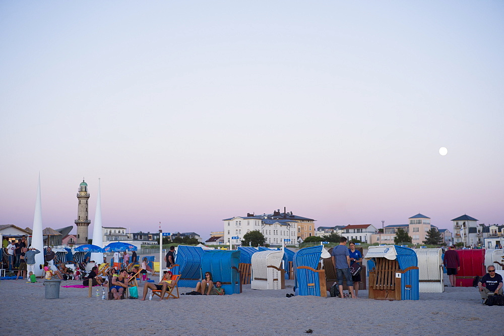 Evening beach life – sunset with a full moon on the sandy beach at Warnemünde, Rostock