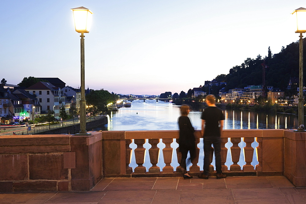 Couple standing on Karl-Theodor Bridge overlooking Neckar at dusk in Heidelberg, Germany