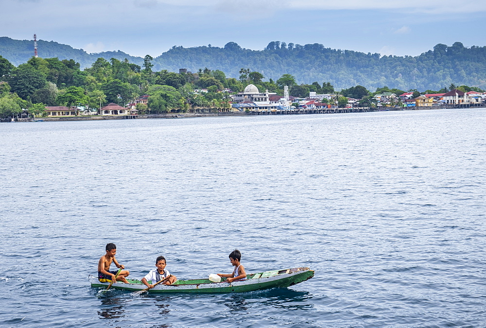 Local boys in a wooden canoe, Rhun, Banda Islands, Maluku, Spice Islands, Indonesia, Southeast Asia, Asia