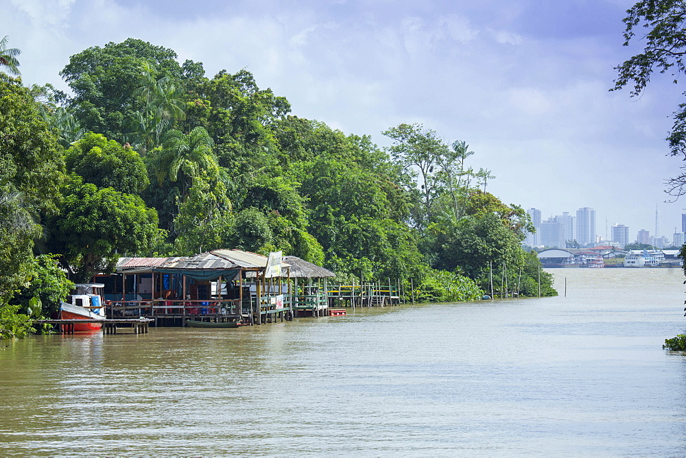 Boats and stilt house on an igarape (flooded creek) in the Brazilian Amazon with Belem city behind, Para, Brazil, South America