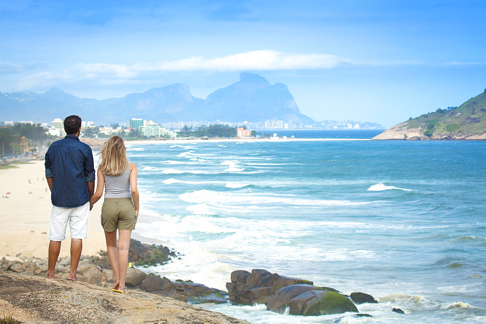 A young couple looking out over Pontal beach, Barra da Tijuca and the Pedra da Gavea, Rio de Janeiro State, Brazil, South America - 1176-275