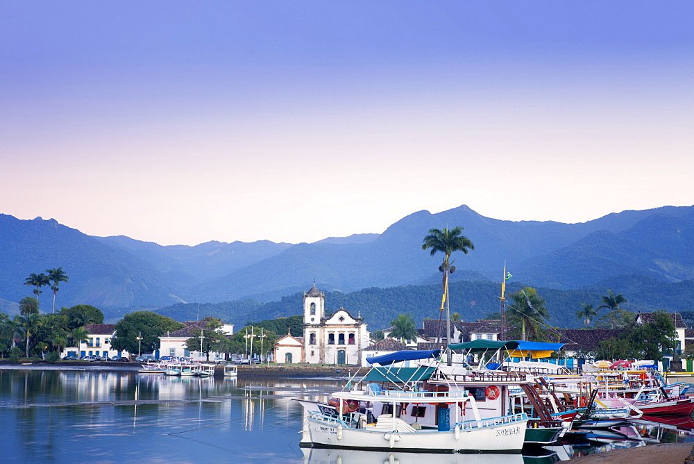 Docks at Paraty with the Serra da Bocaina mountains behind and the church of Nossa Senhora dos Remedios, Rio de Janeiro State, Brazil, South America