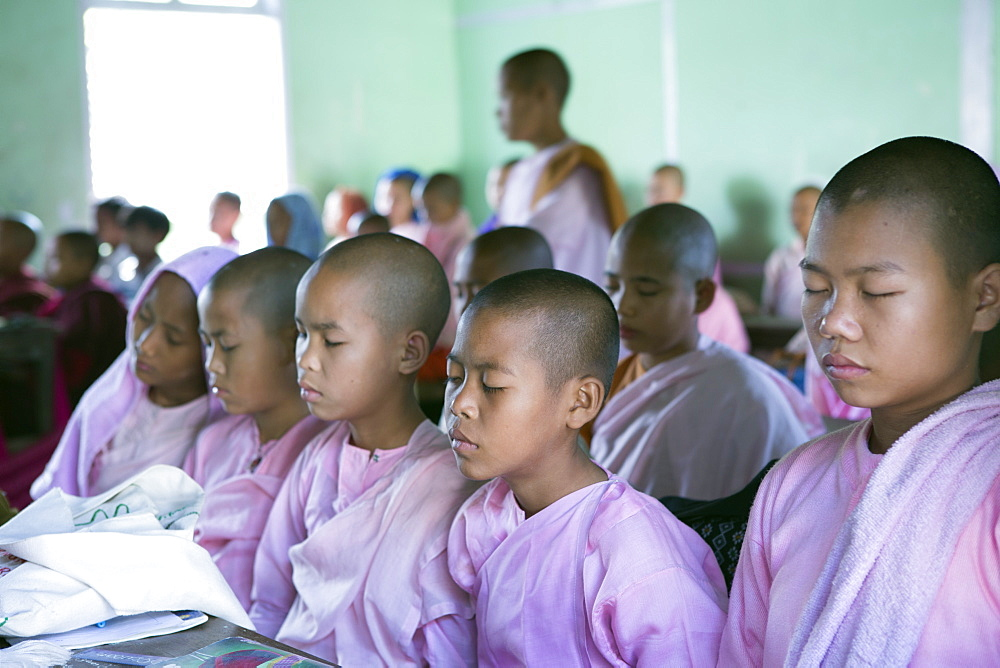 Buddhist novice schoolgirls conducting class meditation in the school classroom before lessons, Sagaing, Myanmar, Southeast Asia