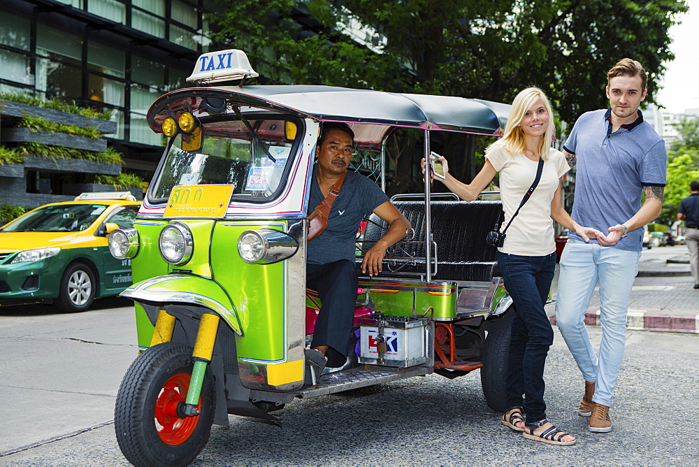 Tourists catching a Tuk-tuk near Khao San road in Bangkok, Thailand, Southeast Asia, Asia