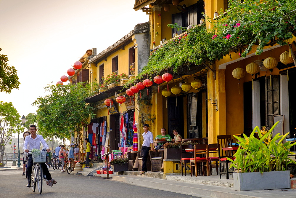 Young couple riding a bicycle past attractive cafe shop houses in Hoi An, Vietnam, Indochina, Southeast Asia, Asia