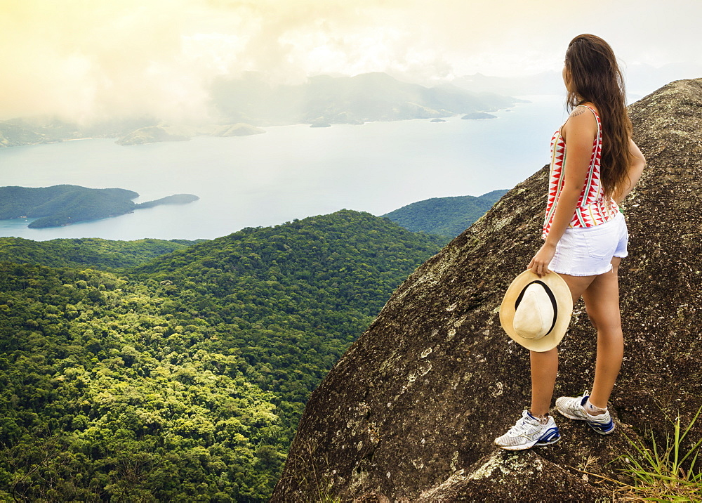 Young woman looking out over the Green Coast (Costa Verde) from Papapagaio peak (Pico do Papagaio) on Ilha Grande island, Rio de Janeiro state, Brazil, South America