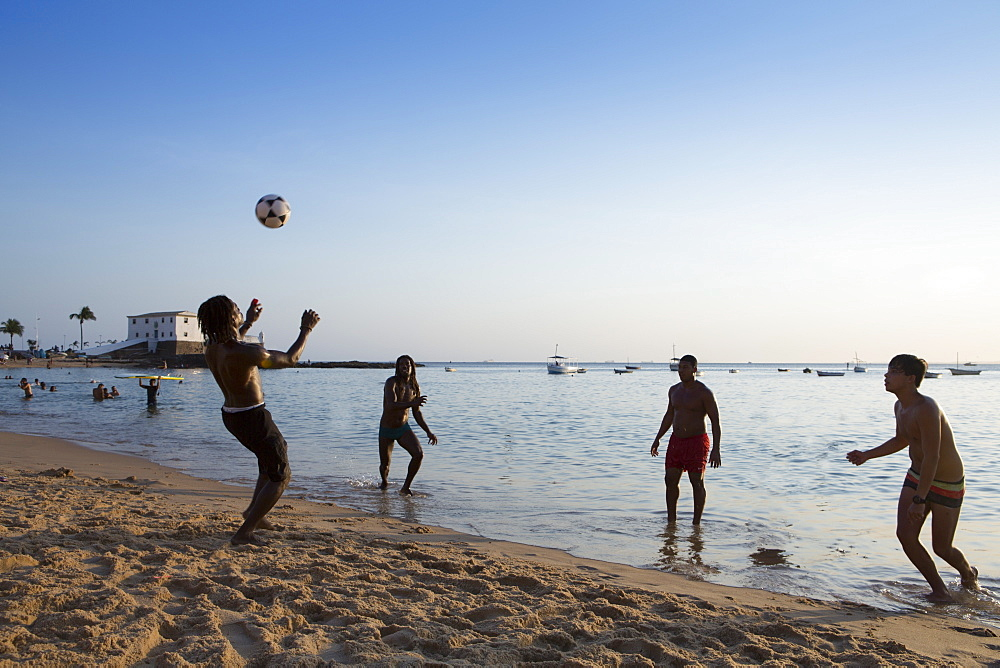 Locals playing football on Barra beach, Salvador, Bahia, Brazil, South America