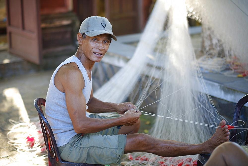 Vietnamese fisherman mending a net - 1176-850