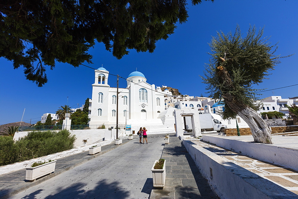 Tourists admire the architecture of Orthodox churches colored white and blue as symbols of Greece, Ios, Cyclades, Greek Islands, Greece, Europe