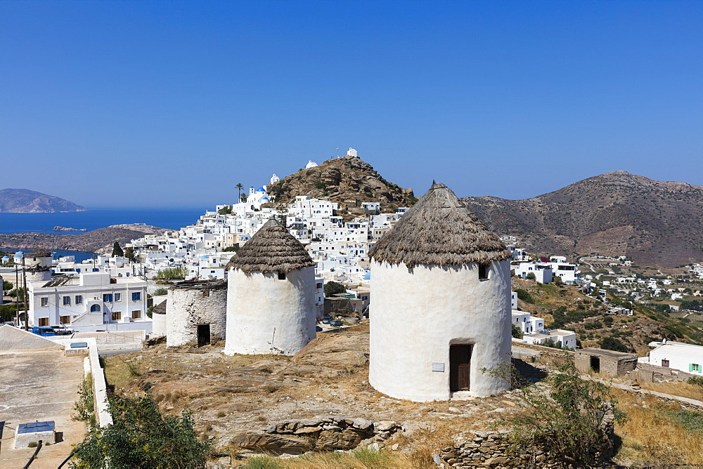A typical Greek village perched on a rock with white and blue houses and quaint windmills, Ios, Cyclades, Greek Islands, Greece, Europe