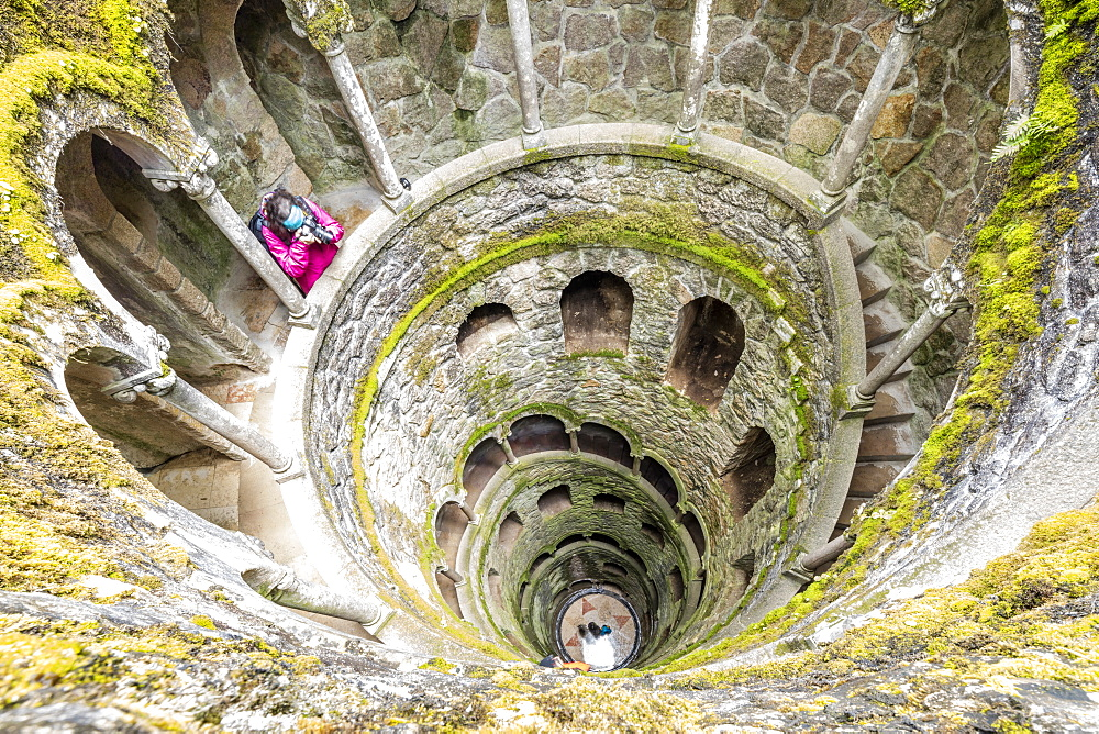 Photographer at the top of the spiral stairs inside the towers of Initiation Well at Quinta da Regaleira, Sintra, Portugal, Europe