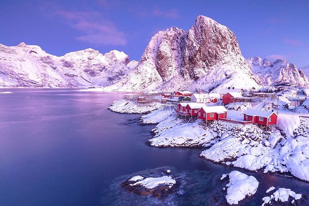 Pink sunrise on snowy peaks surrounded by the frozen sea around the village of Hamnoy, Nordland, Lofoten Islands, Arctic, Norway, Scandinavia, Europe