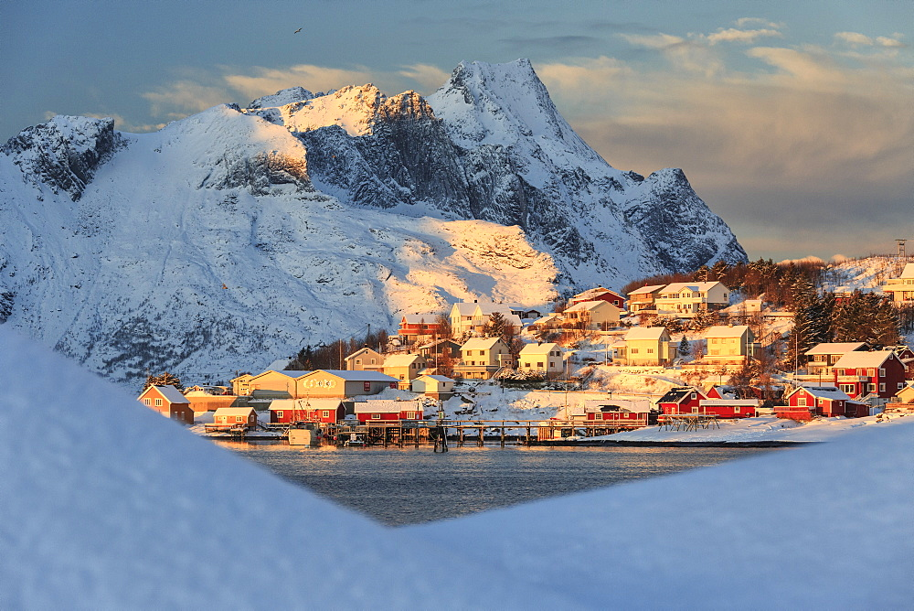 The last rays of sun on the fishing village and the snowy peaks, Kvalvika, Andoya, Reine, Nordland, Lofoten Islands, Arctic, Norway, Scandinavia, Europe