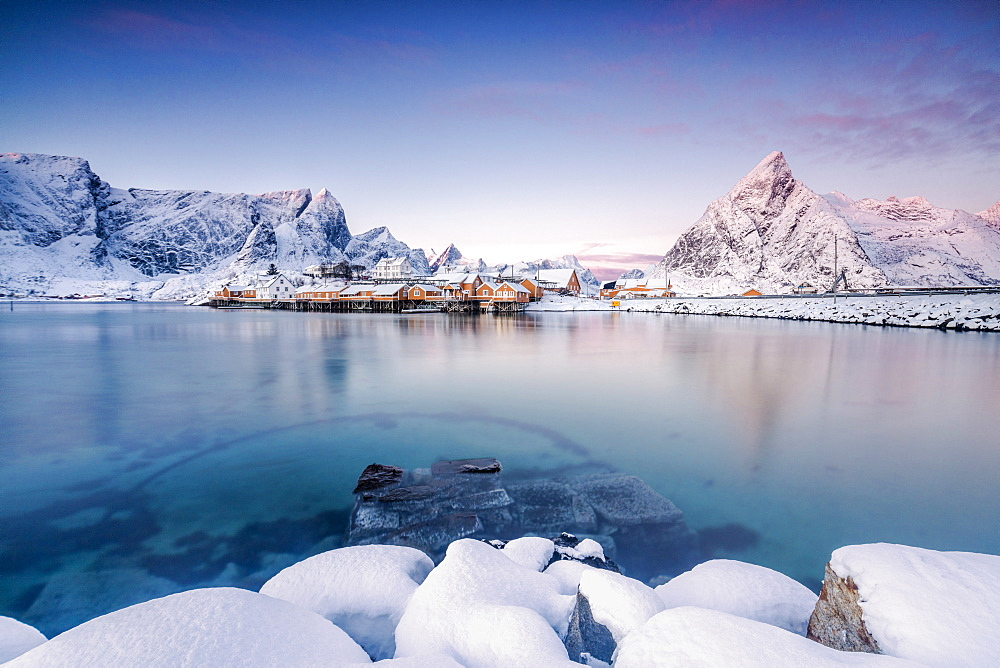 The colors of dawn frame the fishermen's houses surrounded by frozen sea, Sakrisoy, Reine, Nordland, Lofoten Islands, Arctic, Norway, Scandinavia, Europe