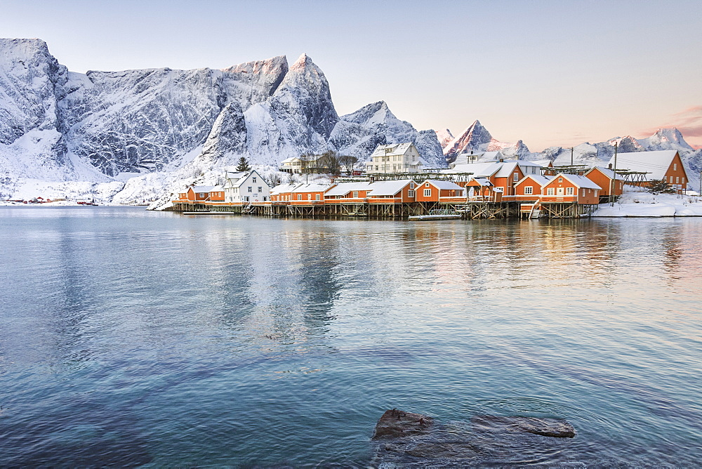 The colors of dawn frame the fishermen's houses surrounded by snowy peaks, Sakrisoy, Reine, Nordland, Lofoten Islands, Arctic, Norway, Scandinavia, Europe