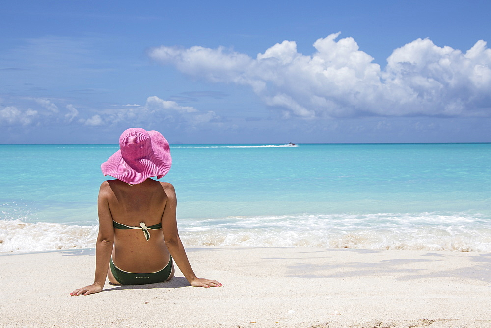 Lady on the sand surrounded by the turquoise Caribbean sea, Jolly Beach, Antigua, Antigua and Barbuda, Leeward Islands, West Indies, Caribbean, Central America