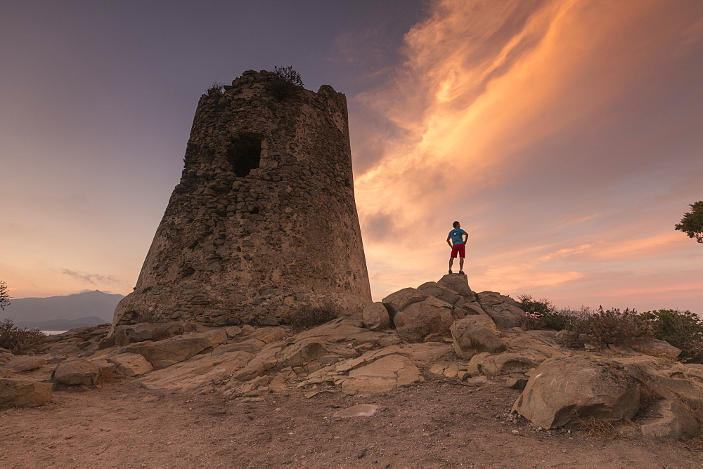 Hiker admires sunset from the stone tower overlooking the bay, Porto Giunco, Villasimius, Cagliari, Sardinia, Italy, Mediterranean, Europe