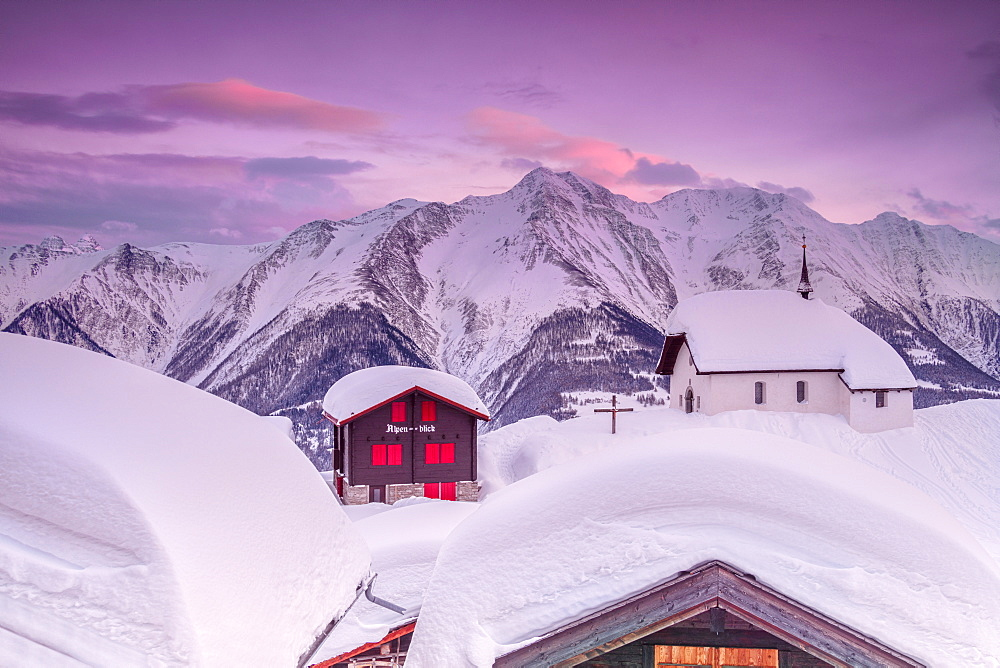 Pink sky at sunset frames the snowy mountain huts and church, Bettmeralp, district of Raron, canton of Valais, Switzerland, Europe