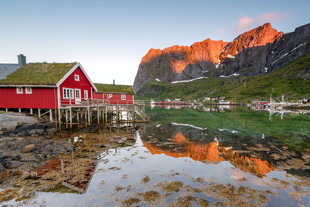 Fishing village and peaks reflected in water under midnight sun, Reine, Nordland county, Lofoten Islands, Arctic, Northern Norway, Scandinavia, Europe