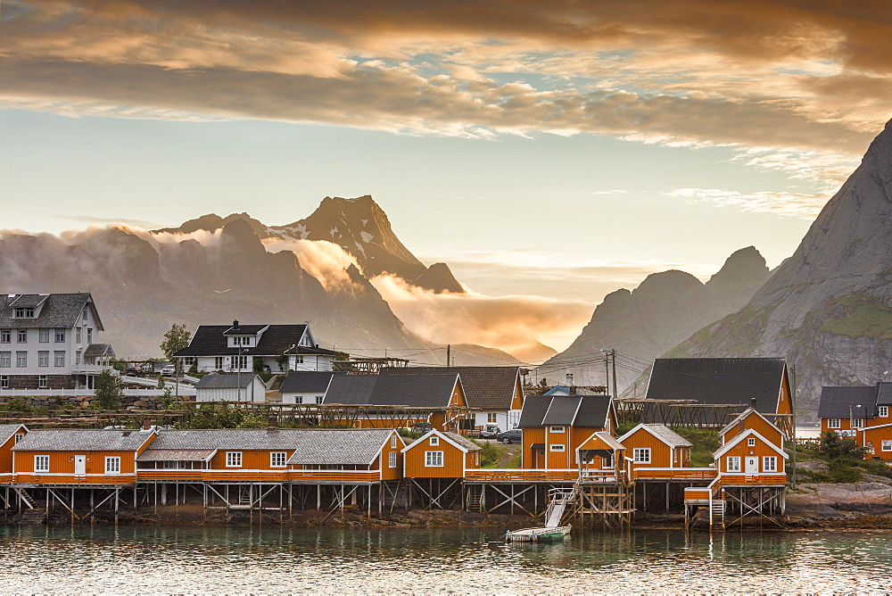 Sunset on the fishing village framed by rocky peaks and sea, Sakrisoya, Nordland county, Lofoten Islands, Arctic, Northern Norway, Scandinavia, Europe