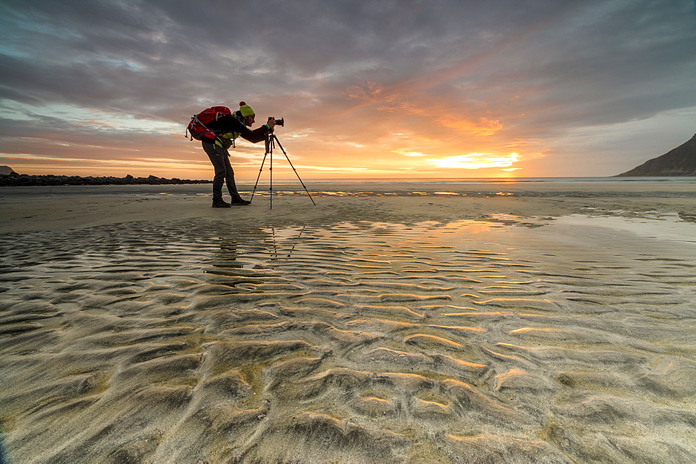 Midnight sun frames photographer in action on Skagsanden beach, Ramberg, Nordland county, Lofoten Islands, Arctic, Northern Norway, Scandinavia, Europe