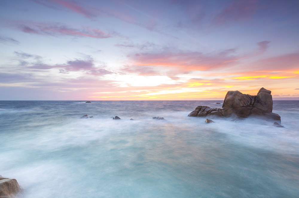 The fiery sky frames the waves crashing on rocks, Capo Testa, Santa Teresa di Gallura, Province of Sassari, Sardinia, Italy, Mediterranean, Europe