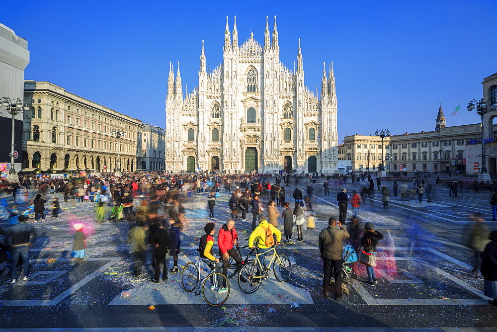 Cyclists in warm spring sun in front of the facade of the Gothic Duomo, Milan, Lombardy, Italy, Europe - 1179-1313