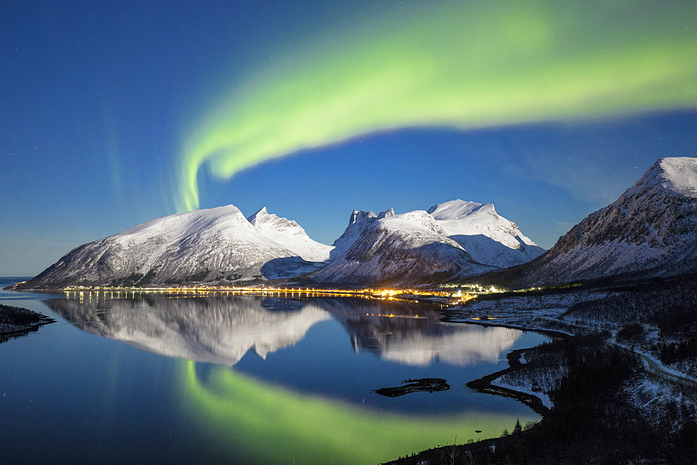 Northern lights (aurora borealis) and stars light up the snowy peaks reflected in the cold sea, Bergsbotn, Senja, Troms County, Norway, Scandinavia, Europe - 1179-1357