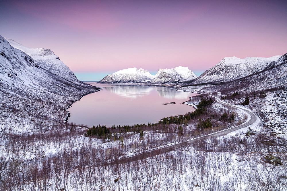 Pink sky at sunrise lights up the snowy peaks reflected in the cold sea, Bergsbotn, Senja,Troms County, Norway, Scandinavia, Europe