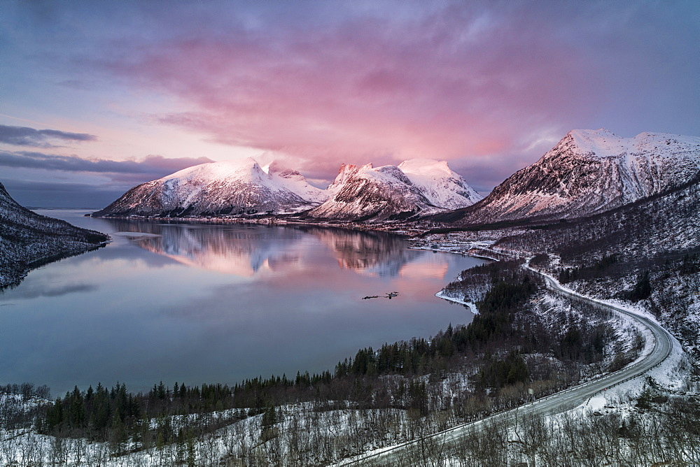 Pink sky and clouds on the snowy peaks reflected in cold sea at sunset, Bergsbotn, Senja, Troms County, Norway, Scandinavia, Europe