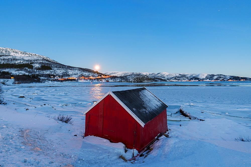 The blue light of dusk on the typical house of fishermen framed by the frozen sea, Fjordbotn, Senja, Troms County, Norway, Scandinavia, Europe