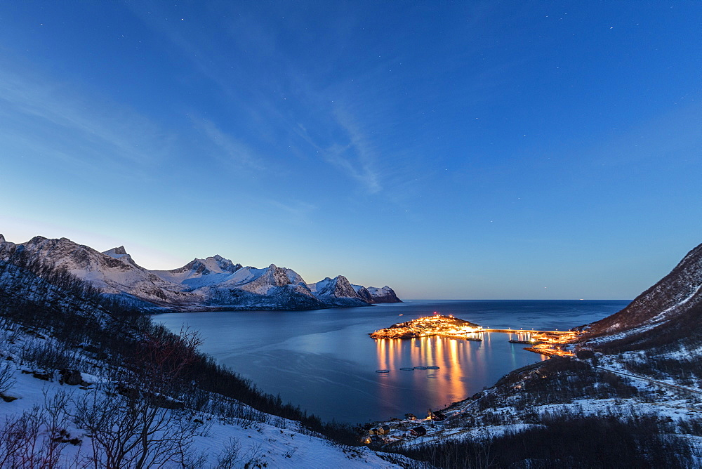Lights on the typical fishing village framed by the frozen sea at dusk, Husoy, Fjordbotn, Senja, Troms County, Norway, Scandinavia, Europe