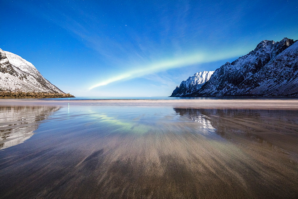 Northern lights and stars light up the sandy beach framed by snowy peaks, Ersfjord, Senja, Troms County, Norway, Scandinavia, Europe