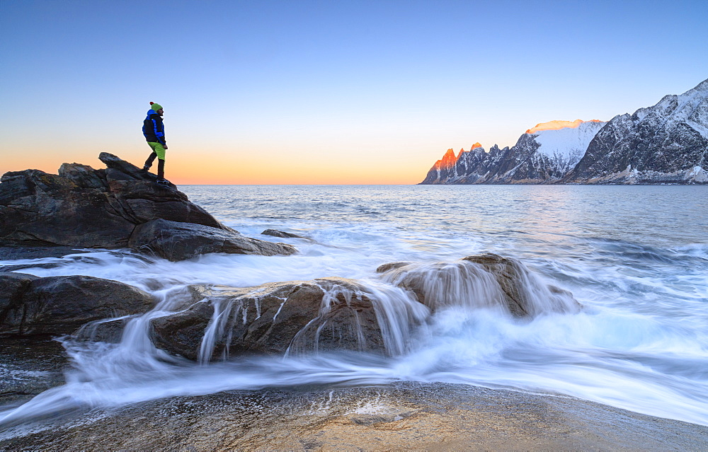 Hiker admires the waves of the icy sea crashing on the rocky cliffs at dawn, Tungeneset, Senja, Troms county, Arctic, Norway, Scandinavia, Europe