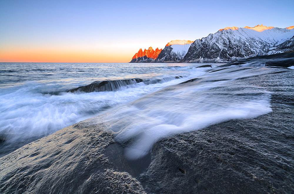 The waves of the icy sea crashing on the rocky cliffs at dawn Tungeneset, Senja, Troms county, Arctic, Norway, Scandinavia, Europe